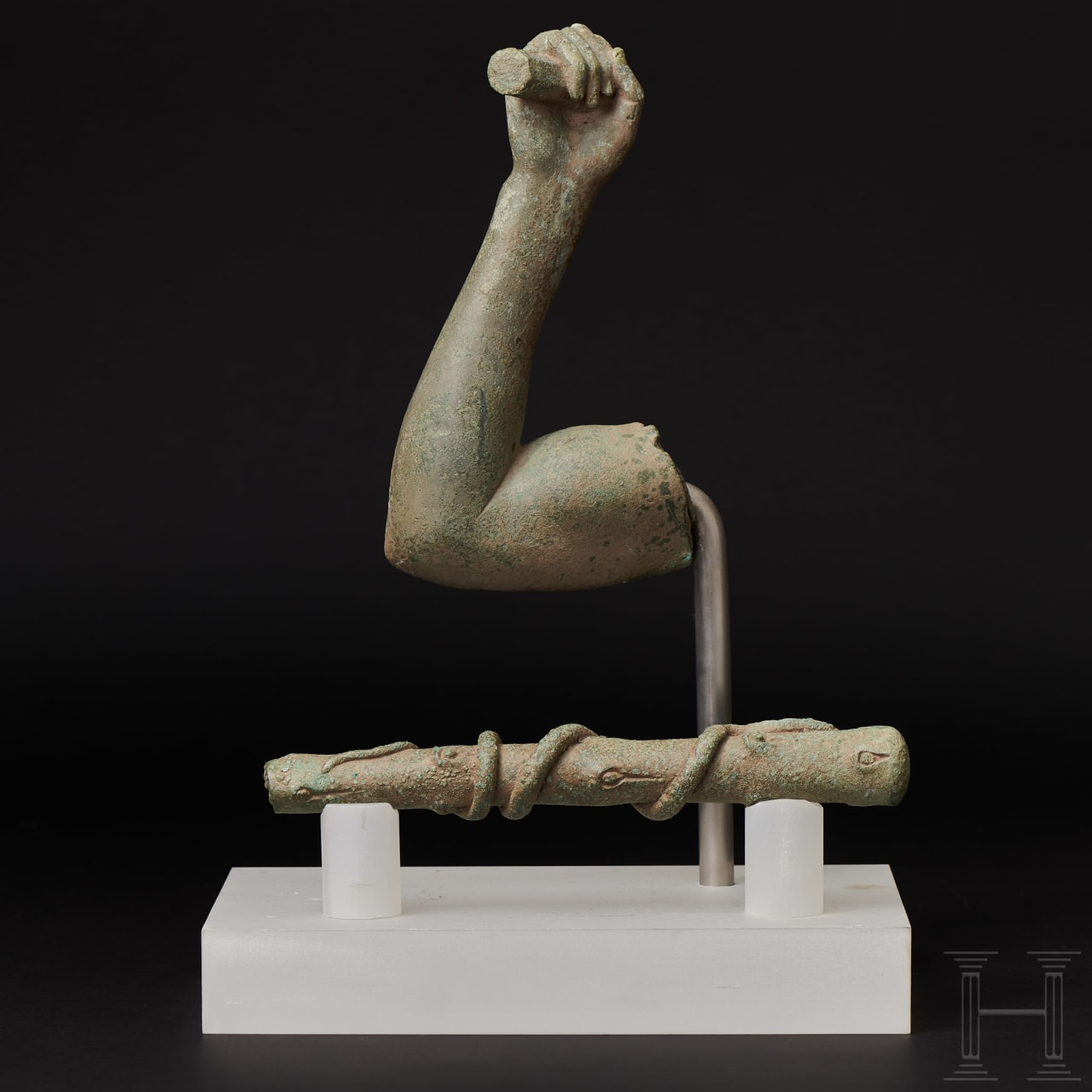 A Roman bronze fragment of an arm and a club on a pedestal, 1st - 2nd century