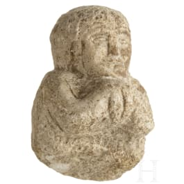A Near Eastern limestone fragment of an offering person, 1st millenium B.C.