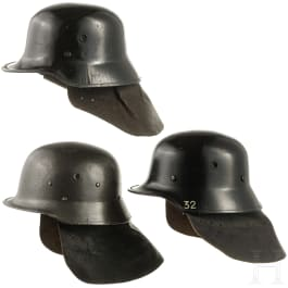 Three fire helmets with shoulder boards, 1950s - 1970s