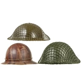Two British type steel helmets and one synthetic helmet, 1940s - 1980s