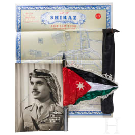 A large photo of King Hussein I, a vehicle standard, a map