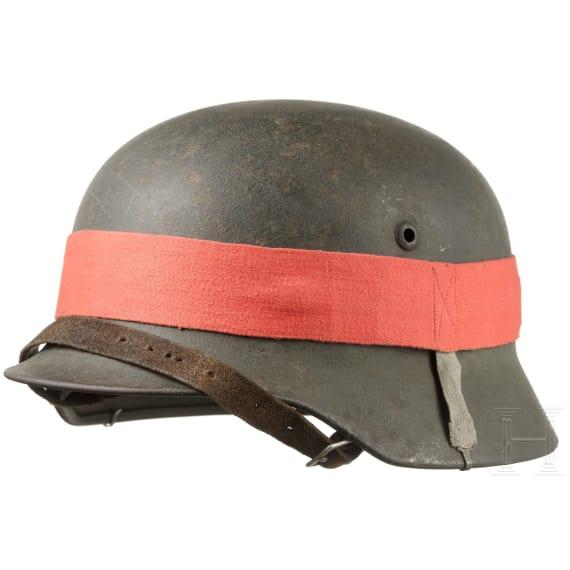 A German steel helmet M 35 with manoeuvre strap, 1935 - 1945