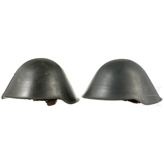 Zwei Stahlhelme mit Helmbezügen, 1960er - 1970er Jahre